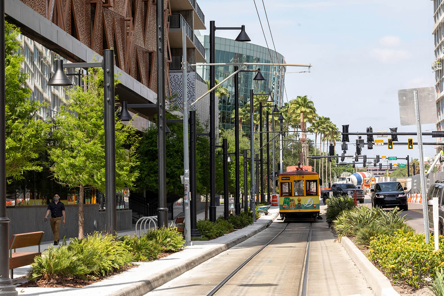 A streetcar glides past a pedestrian down a vegetation-lined track and sidewalk in the Water Street Tampa neighborhood just outside of Heron, a residential building